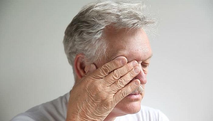 мужчина трет глаз